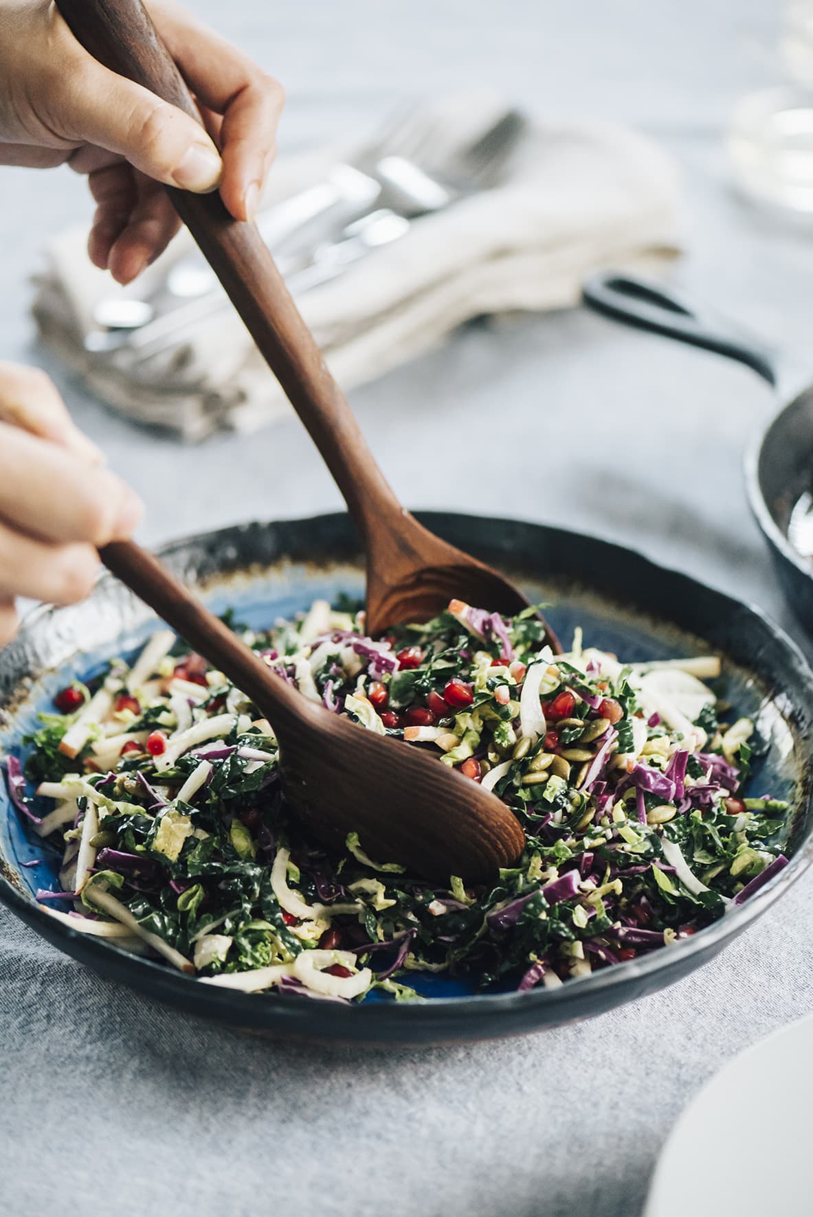 A woman's hands tossing kale pomegranate salad in a blue ceramic bowl.
