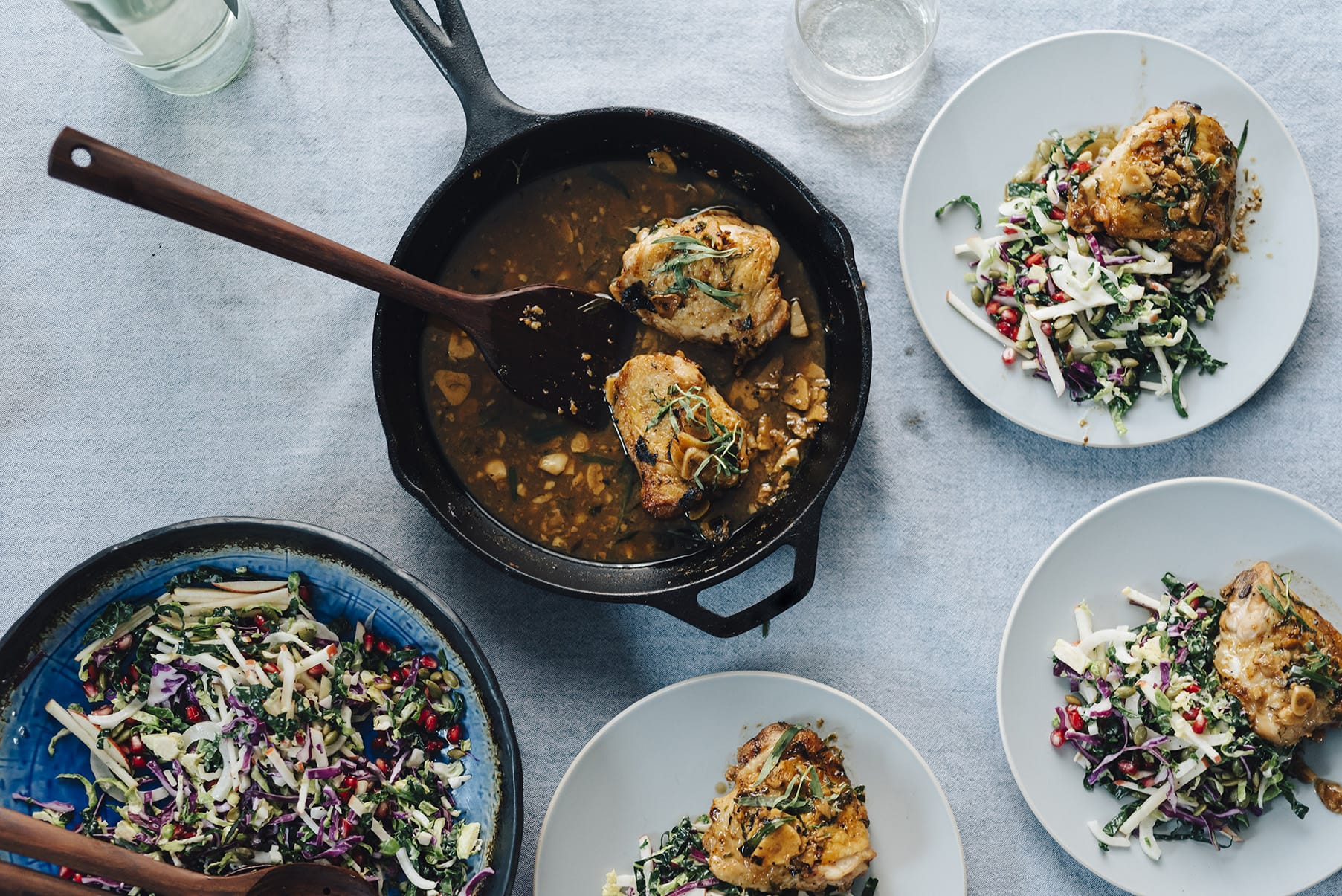 A dinner spread including a bowl of kale pomegranate salad, cast iron skillet chicken, and several dinner plates portioned with chicken and salad.