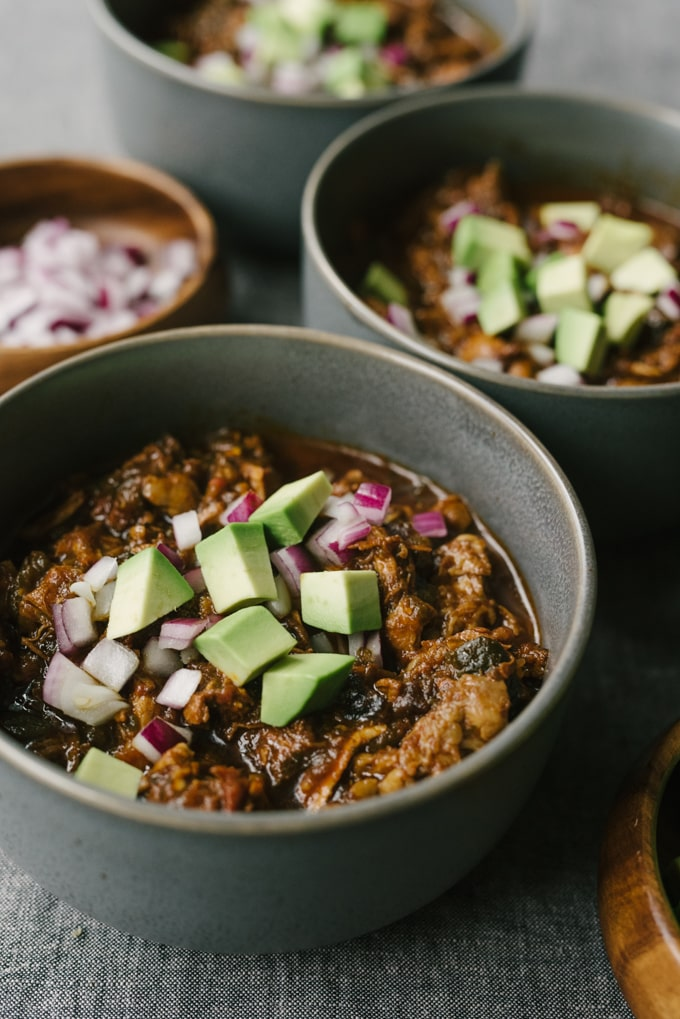 Several bowls of whole30 and paleo chili con carne on a grey tablecloth.