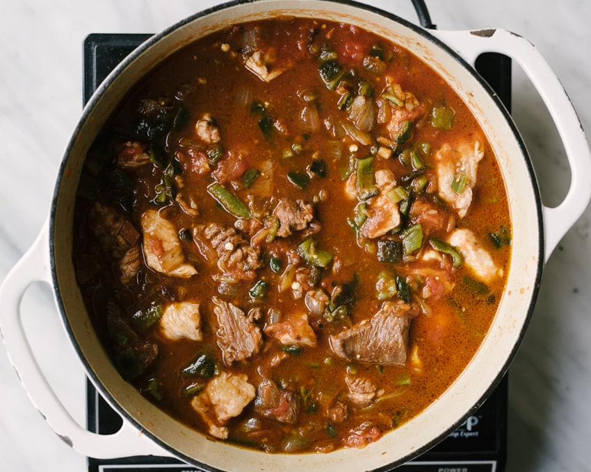 How to make paleo chili con carne. Seared beef and pork, sautéed vegetables, roasted red peppers, and tomatoes in a dutch oven, ready to be slow simmered for tender and flavorful whole30 and paleo chili.