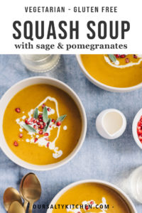 Two bowls of butternut squash soup garnished with pomegranate seeds, sage, and fresh cream on a blue tablecloth.