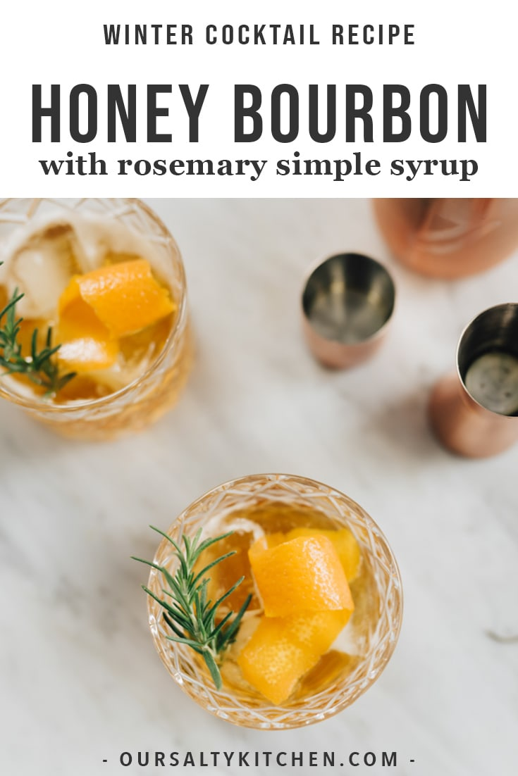 Two honey bourbon cocktails with rosemary simple syrup on a marble table with a bronze cocktail shaker.