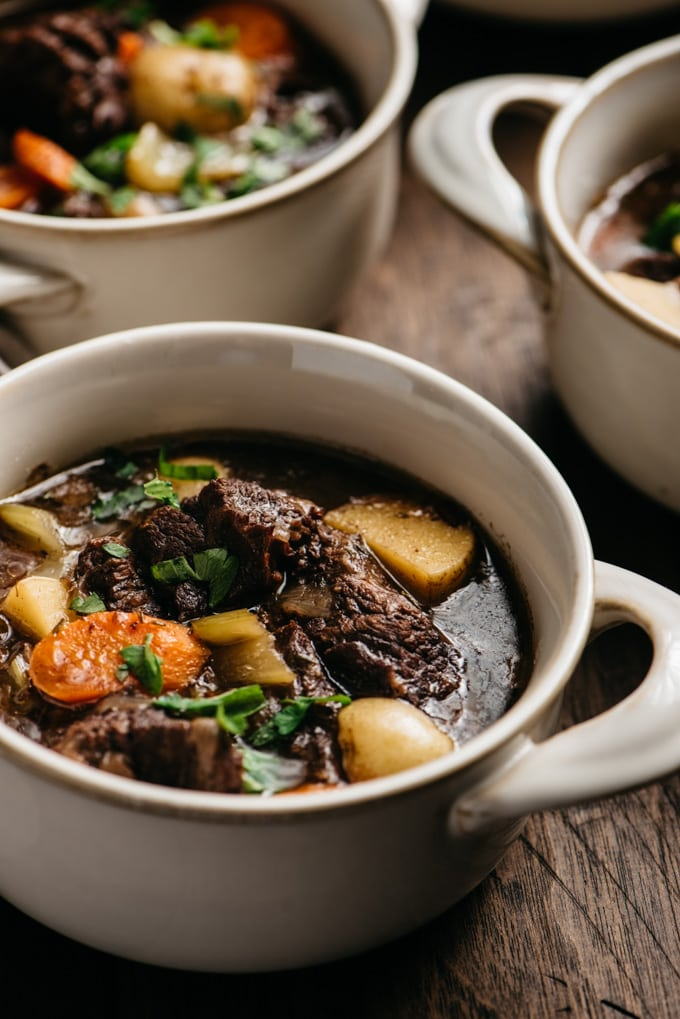 A bowl of dutch oven braised red wine beef stew on a wood table.