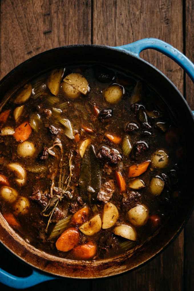 A large blue dutch oven filled with red wine beef stew fresh from the oven.