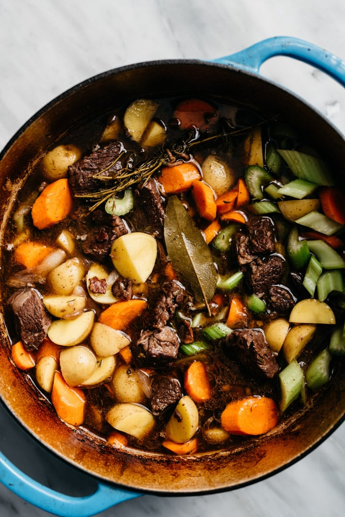 A dutch oven filled with beef braised in red wine with carrots, celery, and onion added to create an oven braised red wine beef stew.