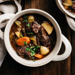 A bowl of one pot red wine beef stew garnished with parsley on a wood table.