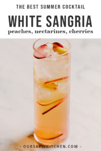 White sangria in a tall glass with various slices of stone fruit.