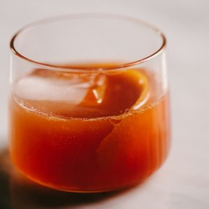 Classic old fashioned cocktail in a rocks glass with an orange peel garnish.