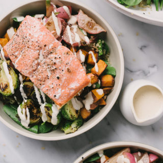 Grain bowls are all the rage, and I love them for both their simplicity and flexibility. This salmon grain bowl is made with leftover roasted vegetables, pan-fried salmon, sesame seeds, tahini dressing, and quinoa. It's a terrific way to use up leftovers and makes for a fast, easy, weeknight dinner.