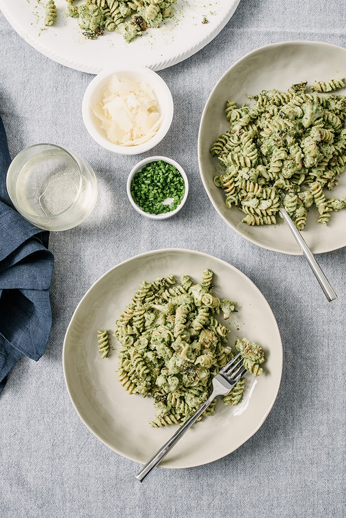 Two bowls of pasta tossed with spinach pesto and roasted cauliflower on a blue tablecloth, with sides of chives, parmesan cheese, and white wine.