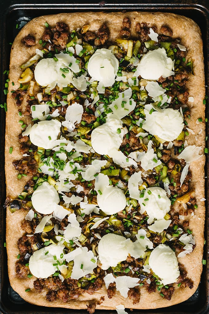 This savory focaccia recipe is an easy crowd pleaser. Layers of ricotta cheese, sweet italian sausage, and caramelized leeks baked atop dense, nutty focaccia bread. It's a super easy, filling, and fun party food.