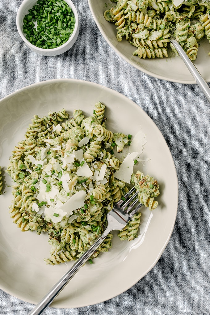 A plate of whole wheat pasta tossed with roasted cauliflower and creamy ricotta spinach pesto, garnished with fresh chives and shaved parmesan cheese.