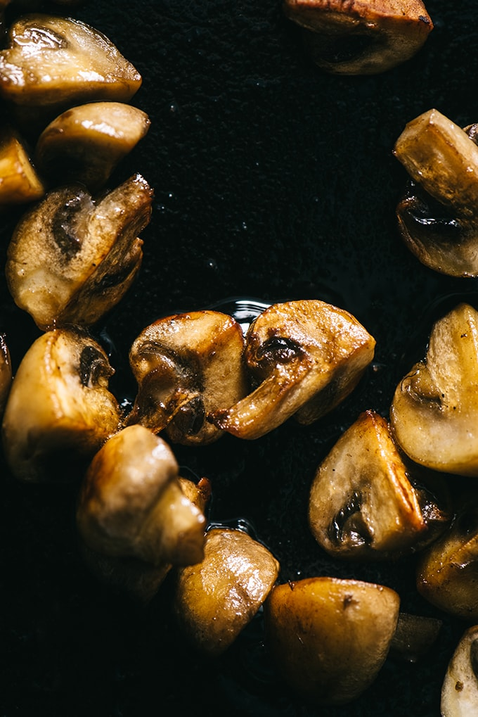 A detail image of crispy, pan seared button mushrooms, a component of vegetarian white bean ragout.