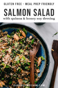 A bowl of salmon quinoa salad with flaked salmon, swiss chard, snap peas, and carrots, finished with a sweet and tangy honey soy vinaigrette.
