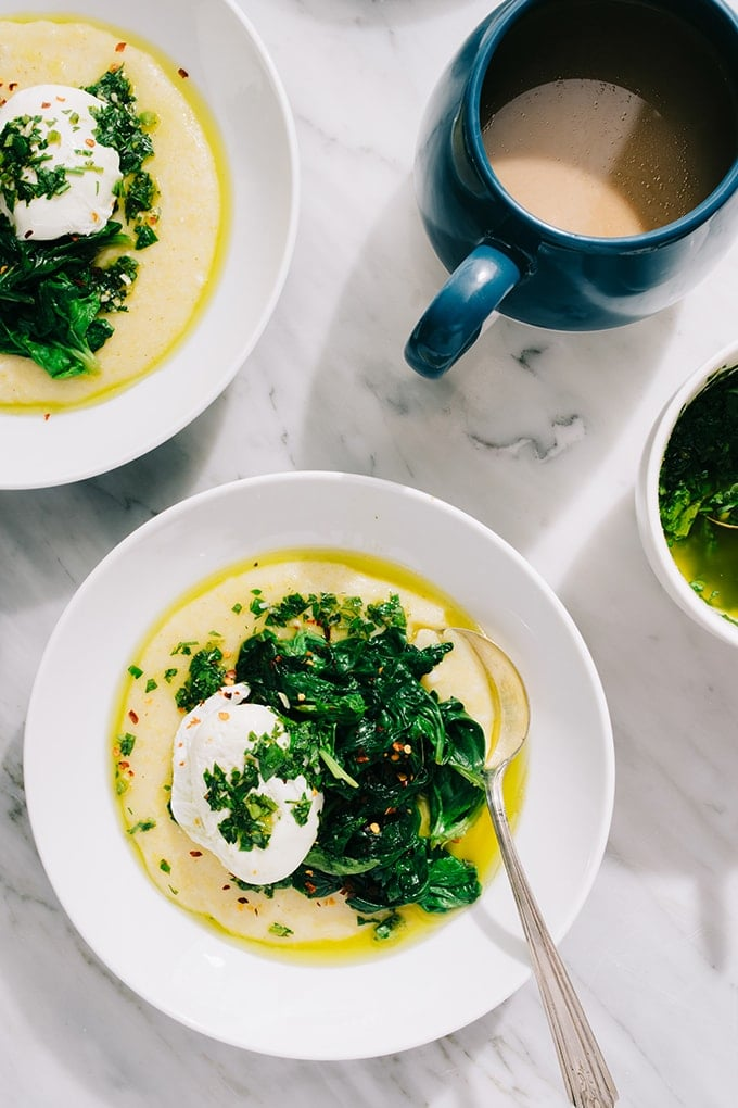 Two bowls of gluten free breakfast polenta topped with a poached egg and sautéed spinach with a blue coffee mug and small bowl of salsa verde.