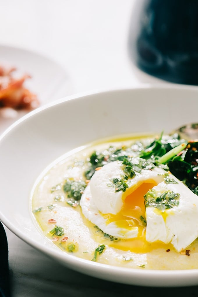 A cracked poached egg over gluten free breakfast polenta with sauteed spinach in a white bowl.