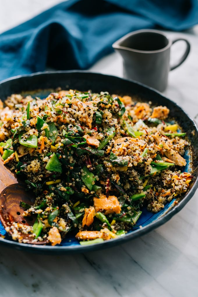 A 45-degree view of a large serving bowl filled with salmon quinoa salad, with a small pitcher of honey soy dressing on the side.