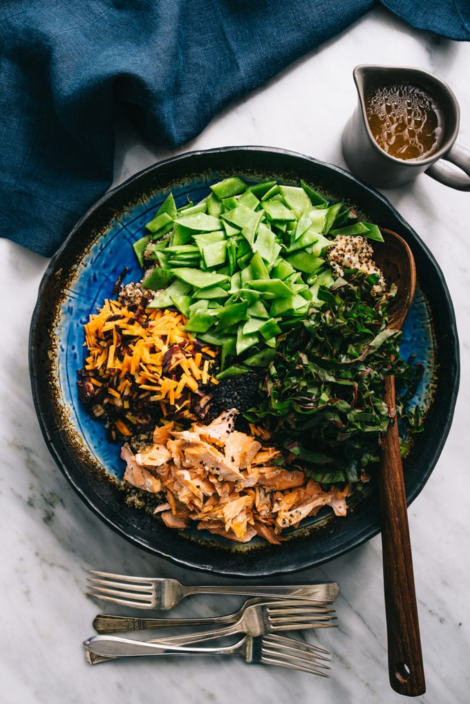 A large serving bowl showing the ingredients in this salmon quinoa salad - flaked salmon, raw carrots, snap peas, and swiss chard - with a small pitcher of honey soy salmon the side.