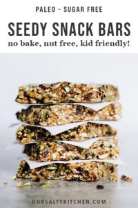 A stack of sugar free paleo snack bars with seeds and dried fruit.