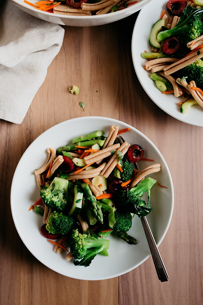 An overhead view of a bowl of broccoli pasta salad on a wood table.