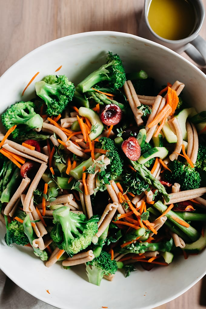 A large white salad bowl filled with healthy broccoli pasta salad with asparagus and cherries, with a side of vinaigrette in a small pitcher.