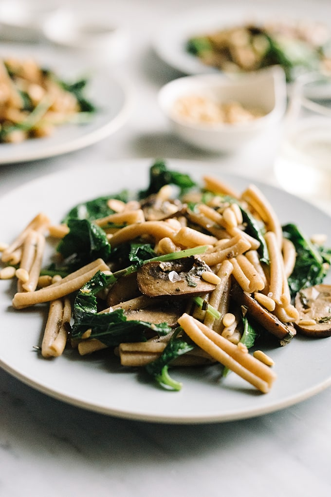 A close-up image of kale mushroom pasta on a blue plate with a marble background.