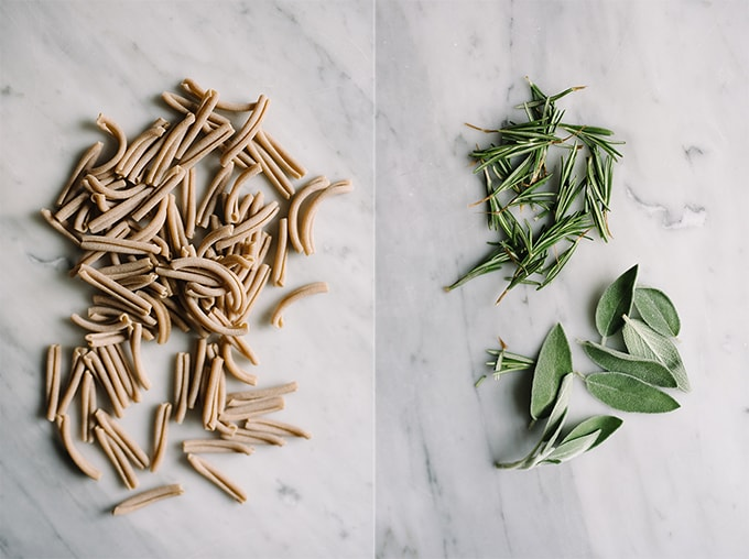 Left - raw whole wheat gemelli pasta noodles on a marble table. Right, fresh rosemary and sage leaves on a marble table for seasoning kale mushroom pasta.