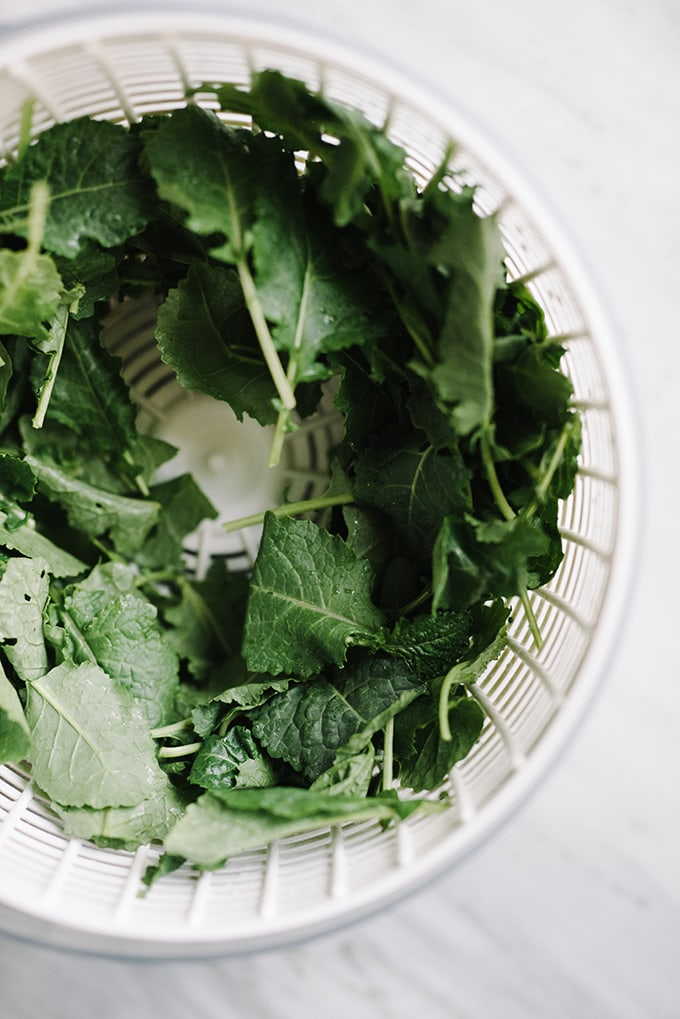 A salad spinner filled with fresh baby kale on a marble table, ready to be tossed into kale mushroom pasta.
