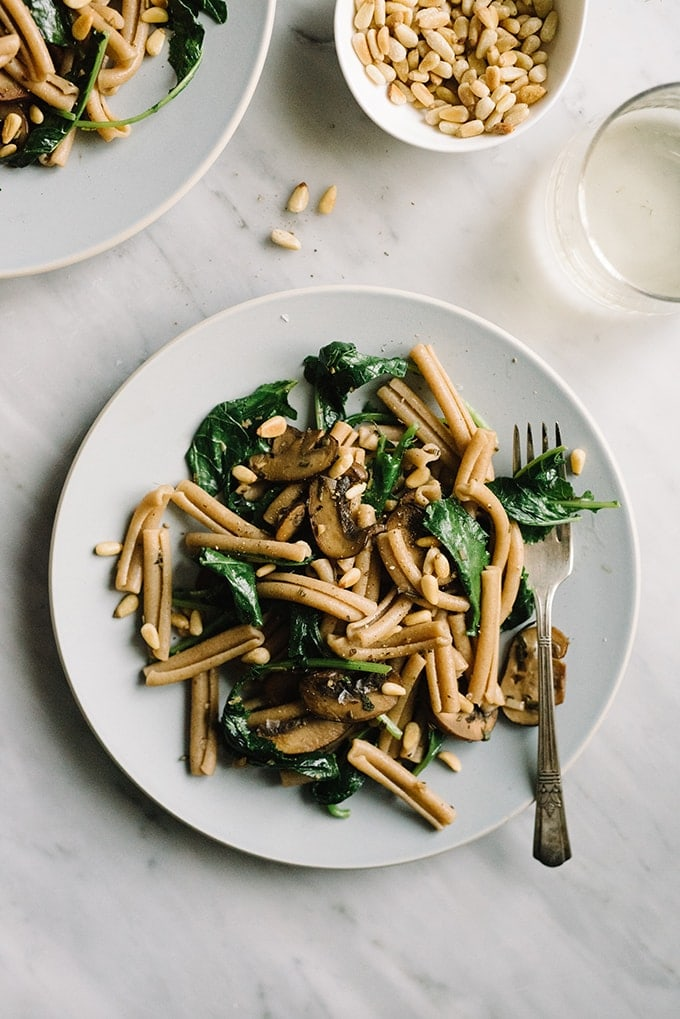 Kale mushroom pasta with toasted pine nuts our salty kitchen a plate of kale mushroom pasta on a blue plate wit a marble background alongside a forumfinder Gallery