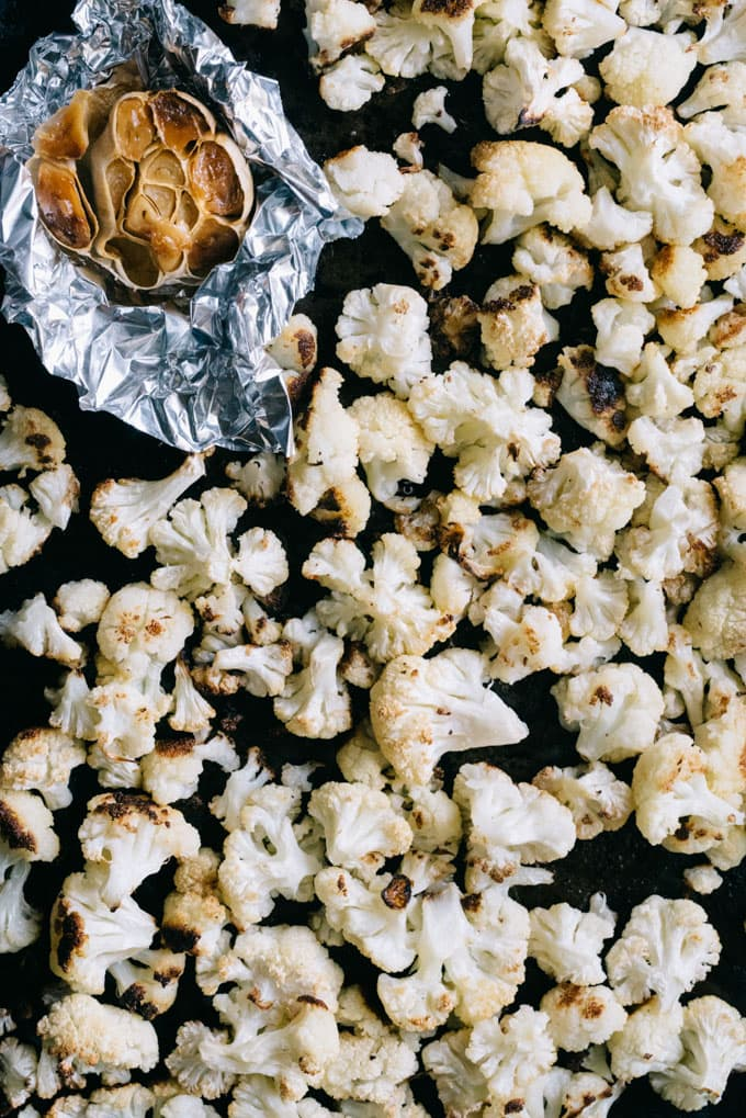 Roasted garlic and roasted cauliflower on a baking sheet, ready to be blended into cauliflower soup.
