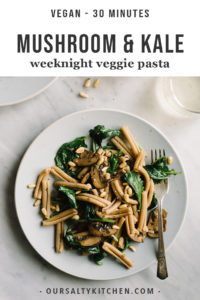A plate of vegan mushroom kale pasta with pine nuts.