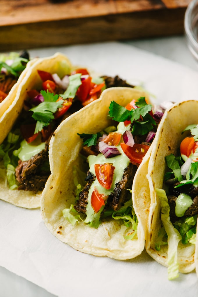 Three gluten free skirt steak tacos topped with cilantro lime crema, diced tomato and red onion, and chopped cilantro.