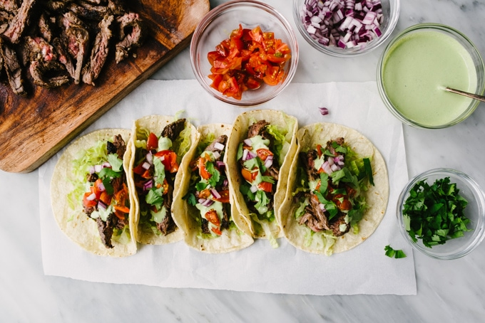 An overhead view of five garnished skirt steak tacos with small bowls of red onion, diced tomato, cilantro, and cilantro lime crema on the side.