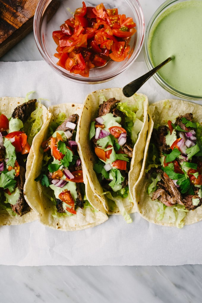 Four skirt steak tacos on a piece of parchment paper with bowls of diced tomatoes and cilantro lime crema on the side.