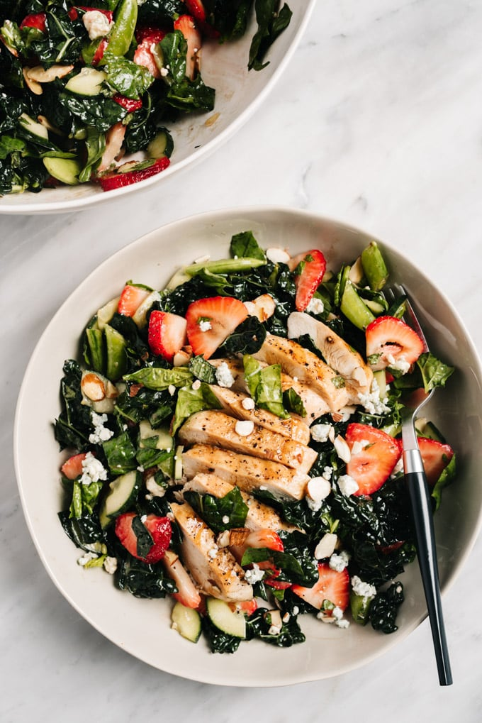 From above, strawberry kale salad in a shallow bowl topped with grilled chicken.