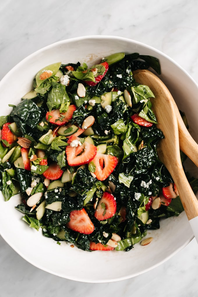 Tossed strawberry kale salad in a large mixing bowl with mint, blue cheese, snap peas, and sliced almonds.