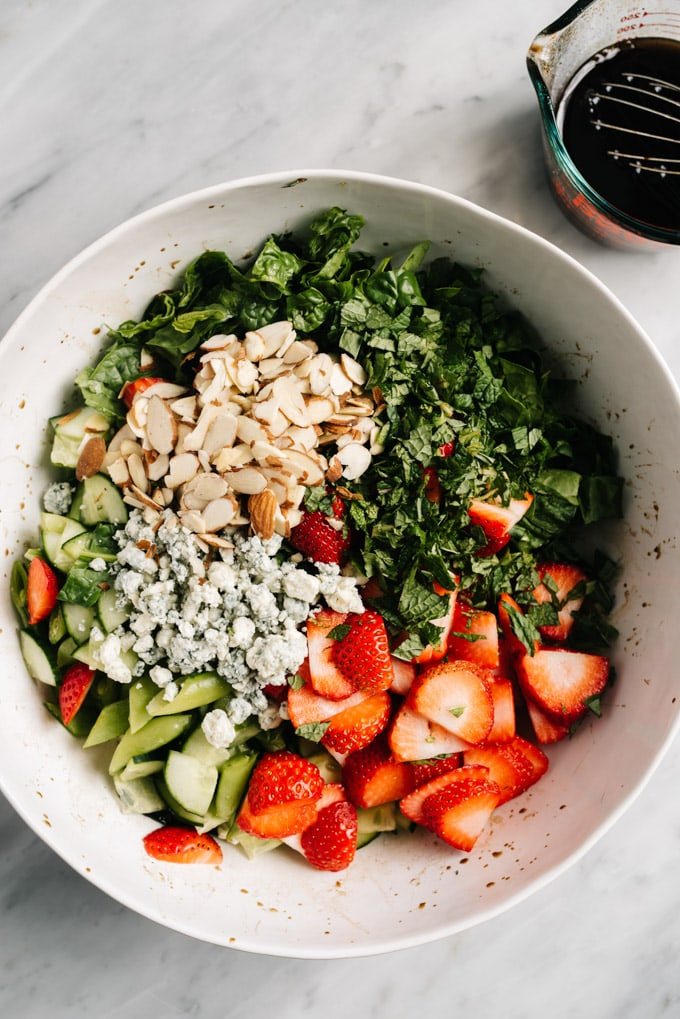 The ingredients for strawberry kale salad in a large mixing bowl from above.