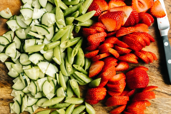 Chopped cucumbers, snap peas, and sliced strawberries on a cutting board.