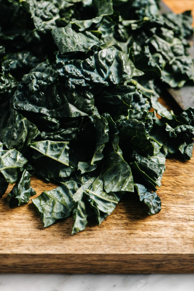 A pile of chopped kale on a cutting board.