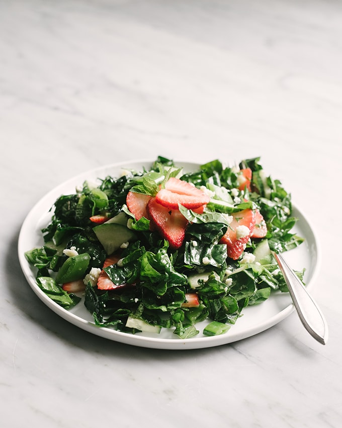 An individual plate of strawberry kale salad on a marble background.