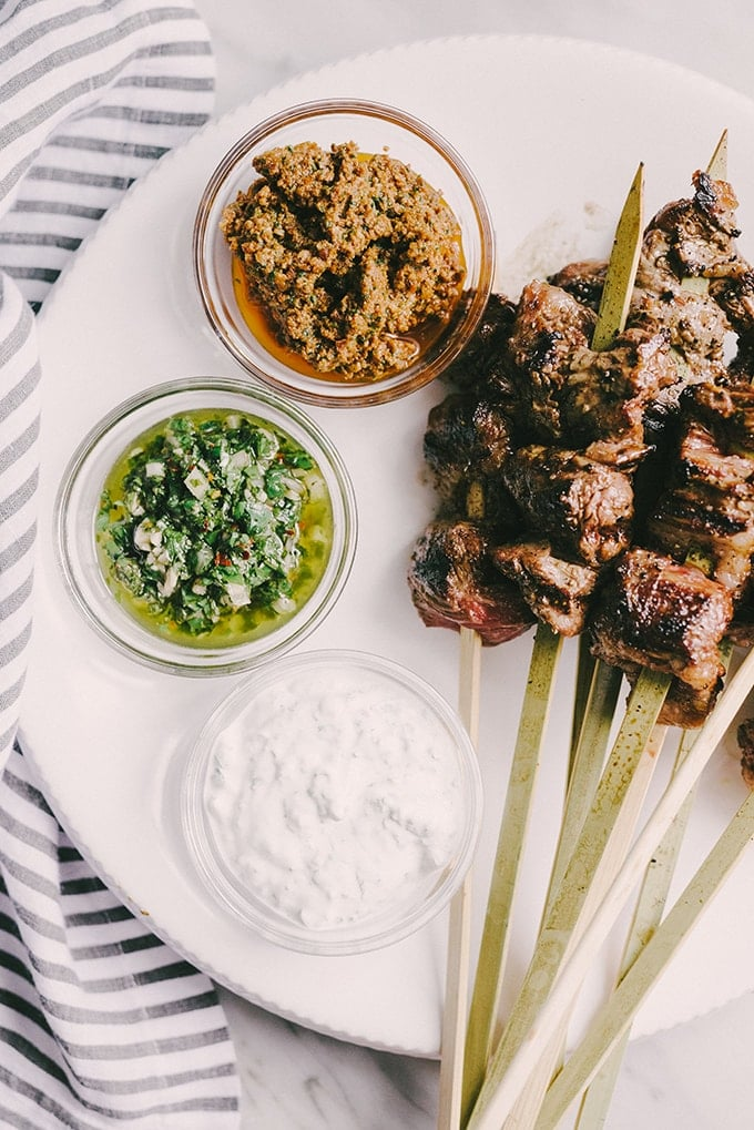 Grilled steak skewers are one of my favorite ways to feed a crowd. They are charred and crispy on the outside, and and tender on the inside. To keep everyone happy, I serve them with a dipping sauce trio of chimichurri, minty yogurt, and sundried tomato pesto.
