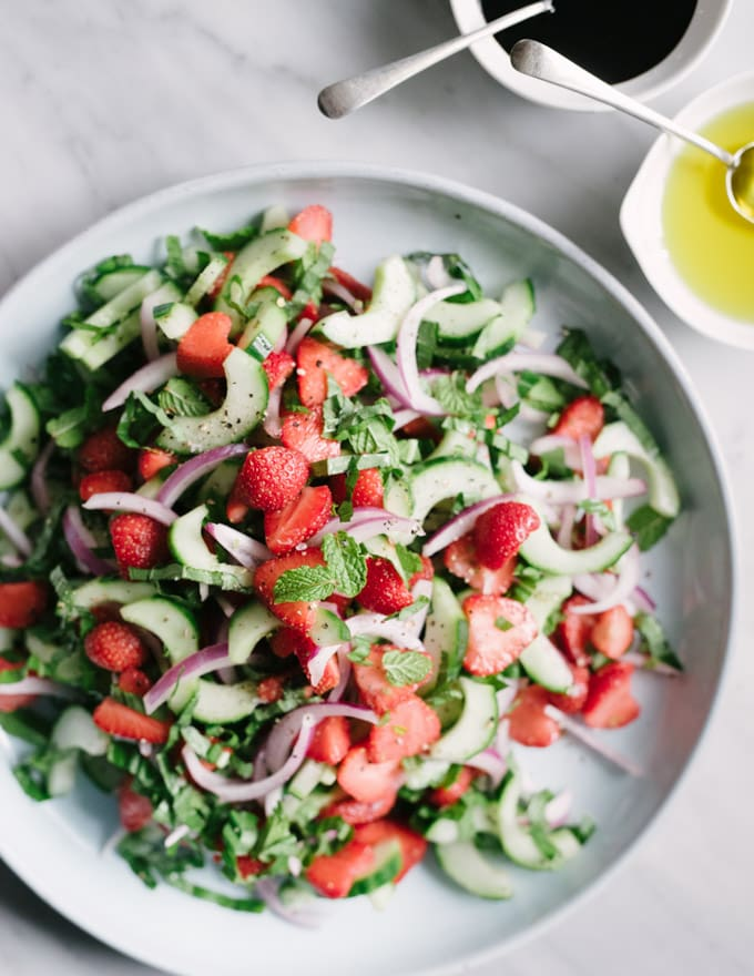 Strawberry cucumber salad with mint and basil on a blue salad plate with small bowls of olive oil and balsamic reduction on the side.