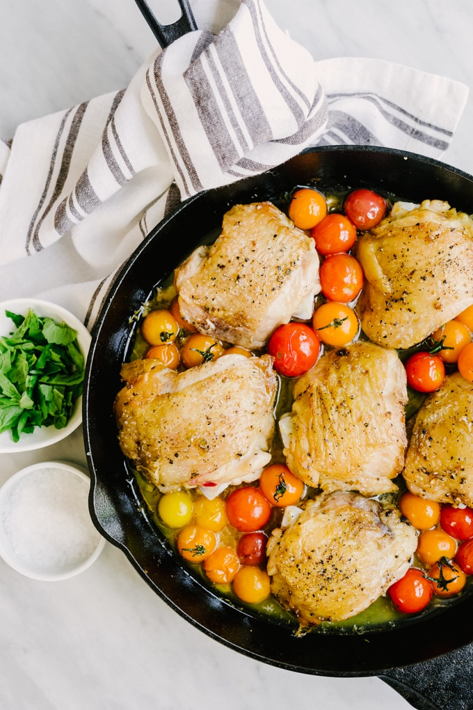 """These crispy chicken thighs are whole foods family favorite. Crispy chicken skin, juicy thigh meat, and sweet tomatoes that burst with a satisfying little """"pop"""". This is an easy, tasty, real food recipe that's on the table in just about 35 minutes. A winning weeknight dinner! #paleo #wholefood #realfood #whole30"""