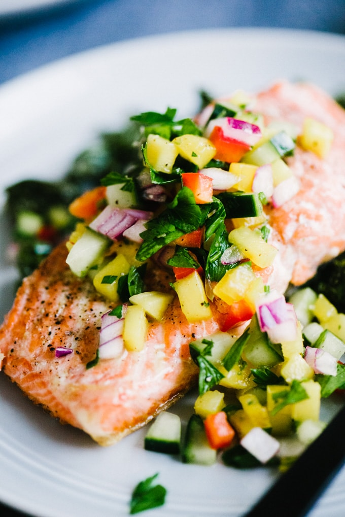 A fillet of pan seared salmon topped with cucumber mango salsa on a grey plate.