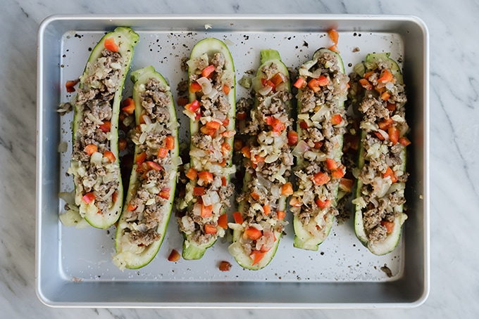 These Italian sausage zucchini boats are an easy, paleo weeknight dinner! They're an easy recipe the entire family will love. #paleo #weeknight #zucchiniboats #stuffedzucchini