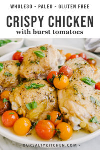 A platter of crispy chicken thighs with burst tomatoes and fresh basil.