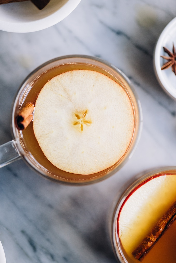 A steaming glass mug of hot toddy with apple cider, garnished with a slice of apple and a cinnamon stick on a marble background.