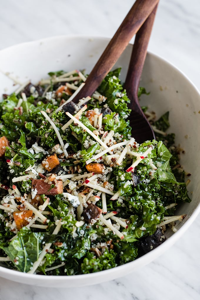 A large white salad bowl on a marble table filled with the base of a kale chicken salad tossed with maple cider vinaigrette.