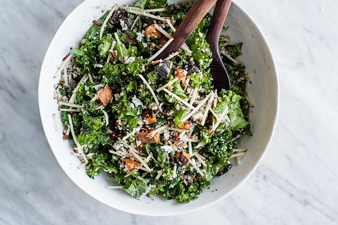 A large white salad bowl filled with the base of kale chicken salad - chopped kale, apples, quinoa, warm potatoes, and a maple cider vinaigrette.