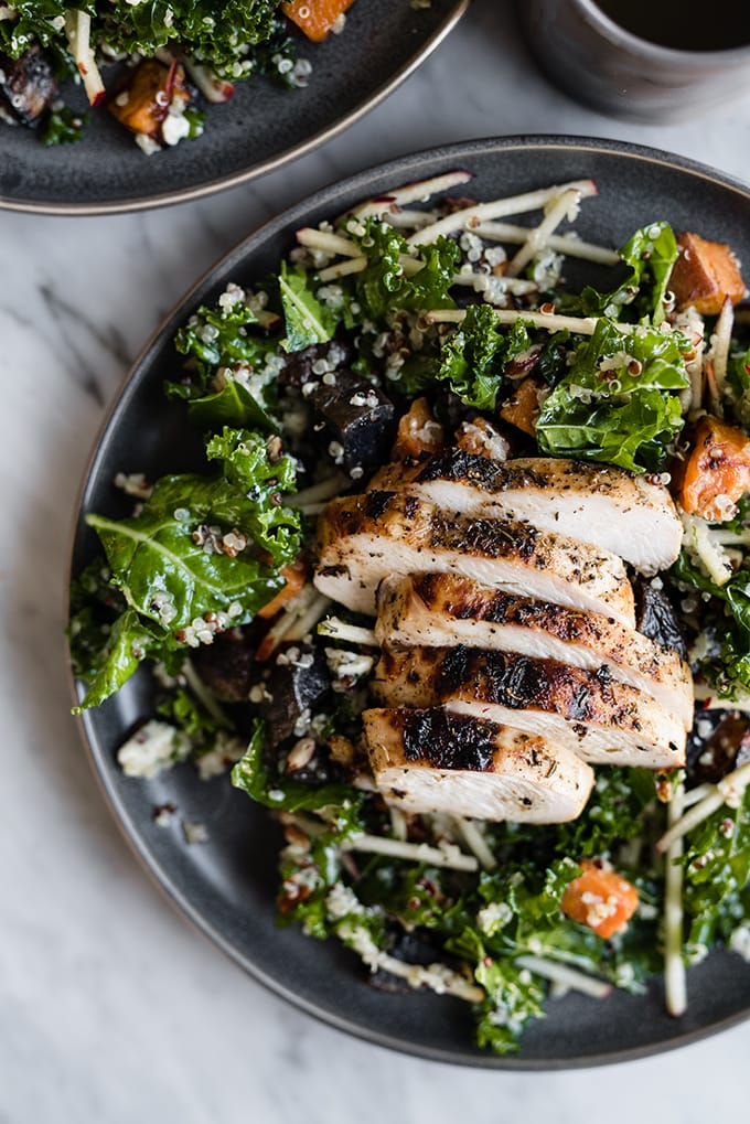 A plate of kale chicken salad, made with kale, apples, quinoa and roasted sweet and purple potatoes.